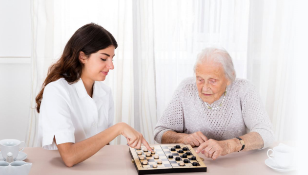 caregiver with senior woman playing chess